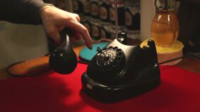 Dialing with an retro rotary phone, man in the office dials the old phone stock video footage
