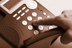 Dialing telephone. Man's hand dialing telephone keypad, sepia tone Royalty Free Stock Images