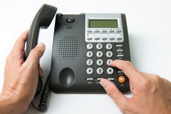 Dialing telephone. Close up of man dialing on a landline telephone Royalty Free Stock Photos