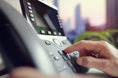 Dialing a telephone in the office Royalty Free Stock Photography