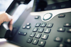 Dialing a telephone in the office. Dialing telephone keypad concept for communication, contact us and customer service support Royalty Free Stock Image