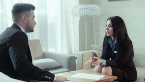 Dialog of the businessman and hotel staff. Dialog of the businessman and female hotel staff manager or consultant in the hall of the hotel, discussing some stock video footage