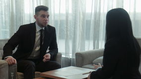 Dialog of the businessman and hotel staff. Dialog of the businessman and female hotel staff manager or consultant in the hall of the hotel, discussing some stock footage