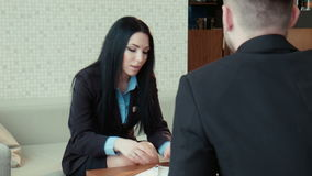 Dialog of the businessman and hotel staff. Dialog of the businessman and female hotel staff manager or consultant in the hall of the hotel, discussing some stock video