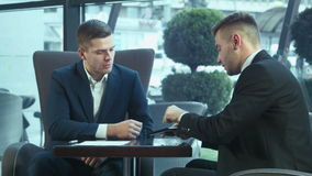 Dialog of businessmans using touchpad. Dialog of two businessmen using touchpad at meeting stock video footage