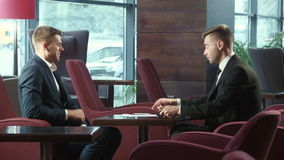 Dialog of businessmans using touchpad. Dialog of two businessmen using touchpad at meeting stock footage