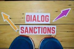Dialog eller sanktioner mitt emot riktningstecken med gymnastikskor på trä royaltyfria foton