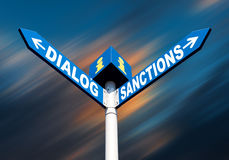 Dialog-Sanctions road sign. Political metaphor concept. Waymark with the words DIALOG and SANCTIONS against abstract blurred background Royalty Free Stock Photo