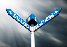 Dialog-Sanctions road sign. Political metaphor concept. Waymark with the words DIALOG and SANCTIONS against dramatic sky with sun rays and dark clouds Royalty Free Stock Image