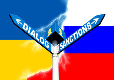 Dialog-Sanctions road sign. Political metaphor concept. Waymark with the words DIALOG and SANCTIONS against of the Ukrainian and Russian flags symbolizing the Royalty Free Stock Image