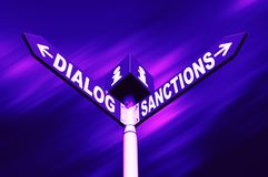 Dialog-Sanctions road sign. Political metaphor concept. Waymark with the words DIALOG and SANCTIONS against abstract blurred background. Trendy neon colors royalty free stock photography