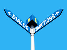 Dialog-Sanctions road sign. Political metaphor concept. Waymark with the words DIALOG and SANCTIONS isolated on blue background Royalty Free Stock Photography