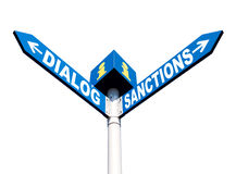 Dialog-Sanctions road sign. Political metaphor concept. Waymark with the words DIALOG and SANCTIONS isolated on white background Stock Image