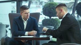 Dialogo dei businessmans facendo uso del touchpad video d archivio