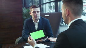 Dialogue of businessmen using the touchpad with the green screen. The businessman explains the business plan and shows to the interlocutor on the touchpad with stock video