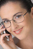 Dialogue by a mobile phone. The young beautiful woman in points, smiling, speaks by phone Stock Photos