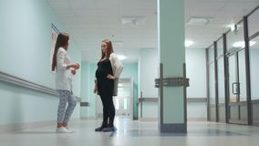 Dialogue between a pregnant woman and a female doctor in the corridor of the hospital. Preparation for childbirth. Consultation on childbirth. Smiling people stock footage