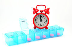 Dialy pill box and red clock on white blackground. Show medicine time concept Royalty Free Stock Photography