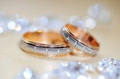 Diamant mit zwei Heiratsgoldringen Stockfotografie