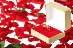 Diamant-Ring in einem Schmucksache-Kasten auf Blumen-Blumenblättern Stockfotografie