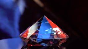 Diamante que gira en una superficie y que oscila en rayos de la luz almacen de video
