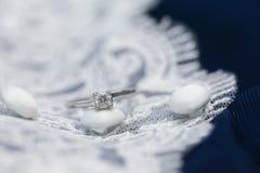 Diamanten bruiloftring op de kleding van het kanthuwelijk stock foto's