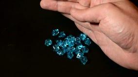 Diamantes o piedra preciosa azules en la mano masculina que cae abajo y la calidad del control metrajes