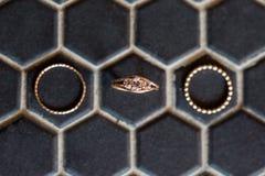 Diamantförlovningsring- och bröllopmusikband på svart sexhörningsbakgrund royaltyfri foto