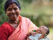 DIAMANTHAMN, INDIEN - APRIL 04, 2013: Den lantliga indiska kvinnan med barnet i händer och i röd sari ler Arkivfoto