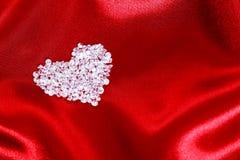 Diamanthjärta på röd satäng arkivfoton