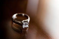 Diamantring auf hölzerner Tabelle Stockfotografie