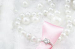 Diamantring en roze lint op de achtergrond van de parelhalsband Royalty-vrije Stock Afbeelding