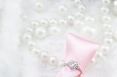 Diamantring und rosa Band auf Perlenhalskettenhintergrund Lizenzfreies Stockbild