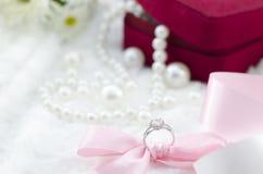 Diamantring und rosa Band auf Perlenhalskettenhintergrund Stockbild