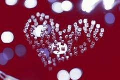 Diamants dans la forme du coeur sur le rouge Jour du ` s de Till Valentine Photographie stock