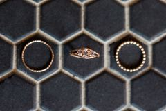 DiamantVerlobungsring und Hochzeitsbänder auf schwarzem Hexagonhintergrund lizenzfreies stockfoto