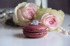 Diamentowy pierścionek na macaron i róż tle Fotografia Royalty Free