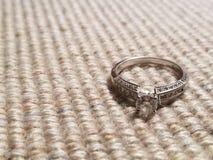 Diamentowy pierścionek zaręczynowy ustawiający przeciw brąz tkaniny tłu obrazy stock
