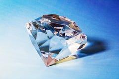 Diamond. Big gem diamond with light reflection on blue background Royalty Free Stock Photography