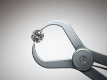 Diamond. Large diamond held by measuring tool stock images