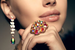 Diamond. Brilliant. Antique old vintage earrings and ring. Jewel. Ry on her finger at the girl close-up on a Royalty Free Stock Images