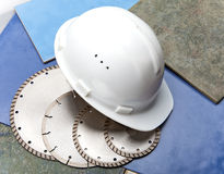 Diamond discs for tile cutting and a helmet on a tile Stock Photos