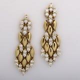 Diamond earrings. Gold and diamond dangle earrings Royalty Free Stock Photography