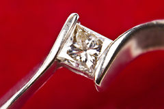 Diamond engagement ring. Close up over red background Royalty Free Stock Photos