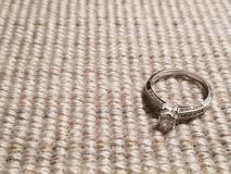 Diamond engagement ring against brown fabric background. stock photo