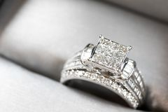 A diamond engagement ring .in a box with glint/reflection. Shimmering princess-cut diamonds. stock photos