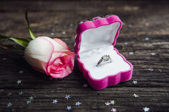 A diamond engagement ring in a jewellery box, shot next to a red rose Stock Images