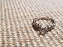 Diamond engagement ring set against brown fabric background. stock images