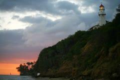 Diamond Head Lighthouse and Coastline. Diamond Head Lighthouse providing guiding light at sunset to ships and boats at sea off the coast of Ohau. The lighthouse Stock Photo