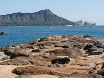 Diamond Head from Waikiki. With lave rocks in the foreground Stock Photo